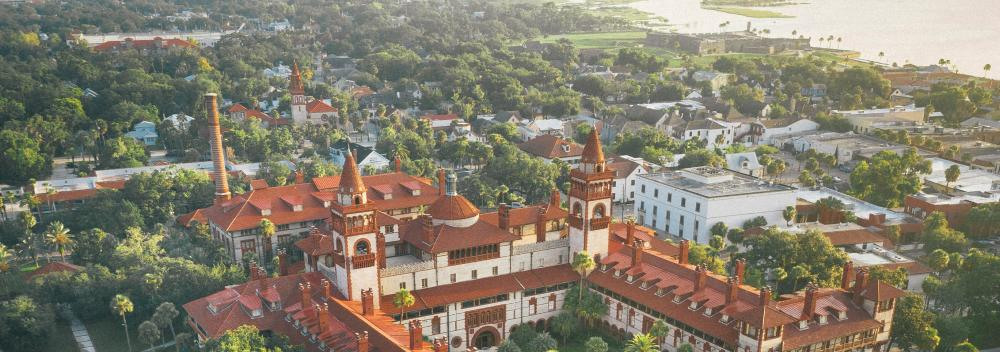 Aerial view of Flagler College with Castillo de San Marcos in the background in St. Augustine, Florida